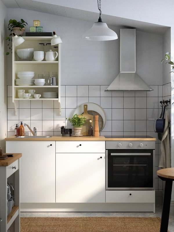 A kitchen with white tiles and grey walls, a white KNOXHULT kitchen with black knobs and appliances in stainless steel.