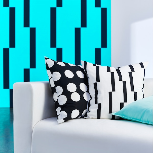 A KLARASTINA cushion cover with polka dots and a KINNEN cushion cover with a geometric pattern, both in black and white.