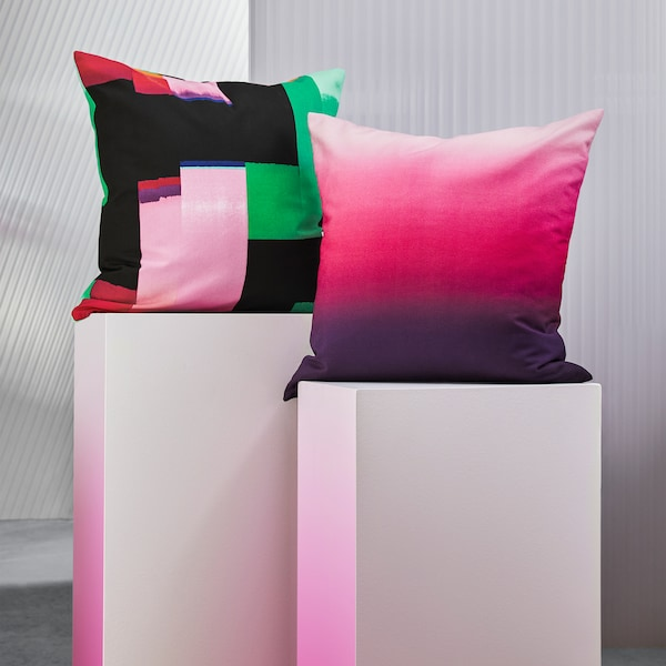 A KLOCKRANKA cushion cover with a multi-colour pixel pattern and a STRÄVKLINT cushion cover with a bold ombre effect.