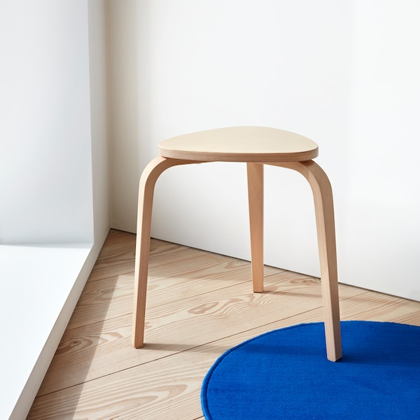 A KYRRE stool made in birch designed in a playful style with a triangle seat and tapered legs.