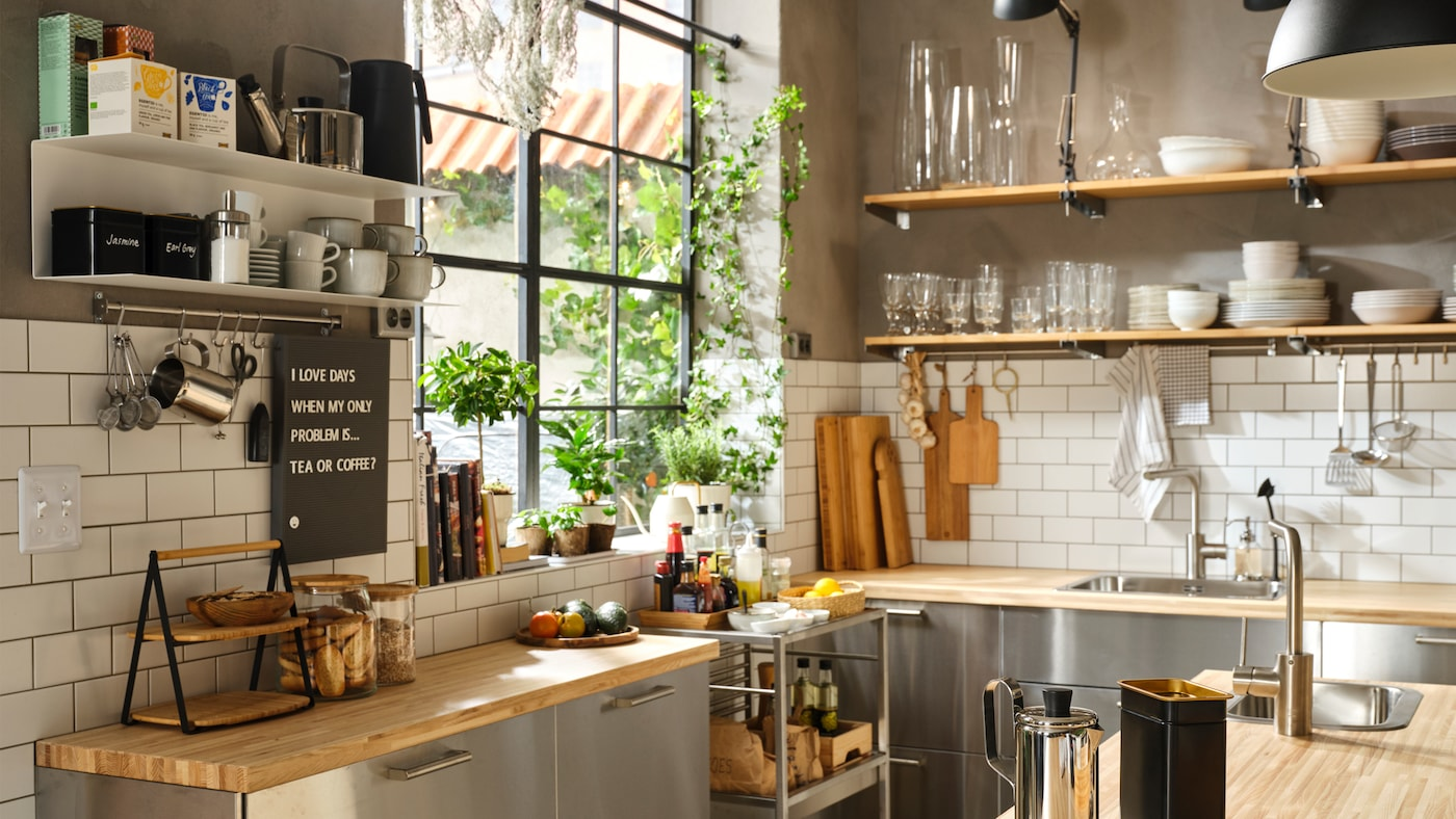 A large, semi-professional kitchen with wooden work tops, stainless steel fronts and open shelves for dinnerware.