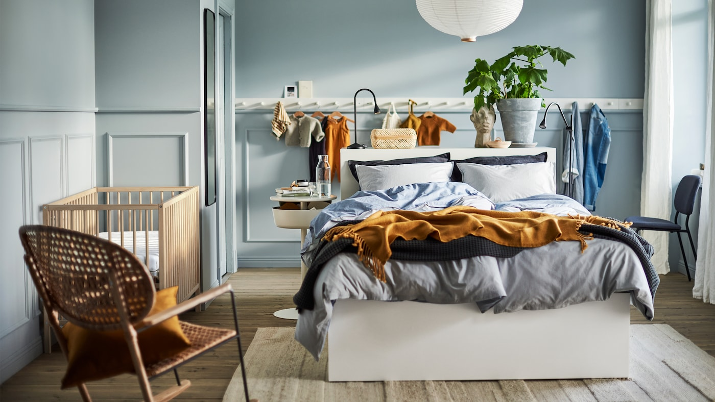 A light blue bedroom with a white bed, a white lamp, a white panel of hooks, a rattan rocking chair and a SNIGLAR baby cot.