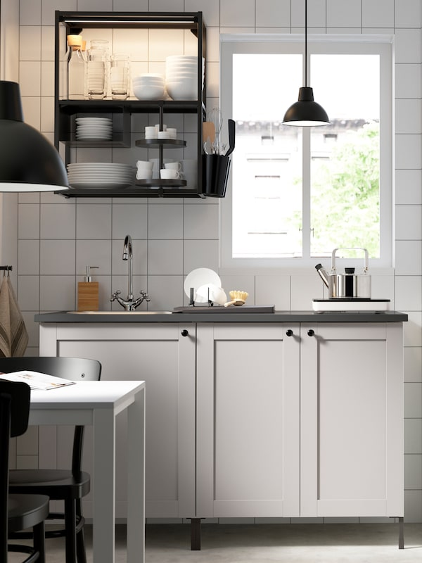 A light drenched kitchen with whit tiles, an ENHET kitchen with white fronts and black shelving, is placed next to a window.
