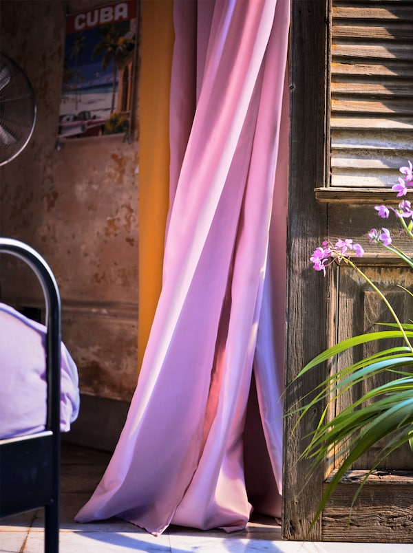 A light purple, air purifying curtain blowing in the wind next to a wooden shutter.