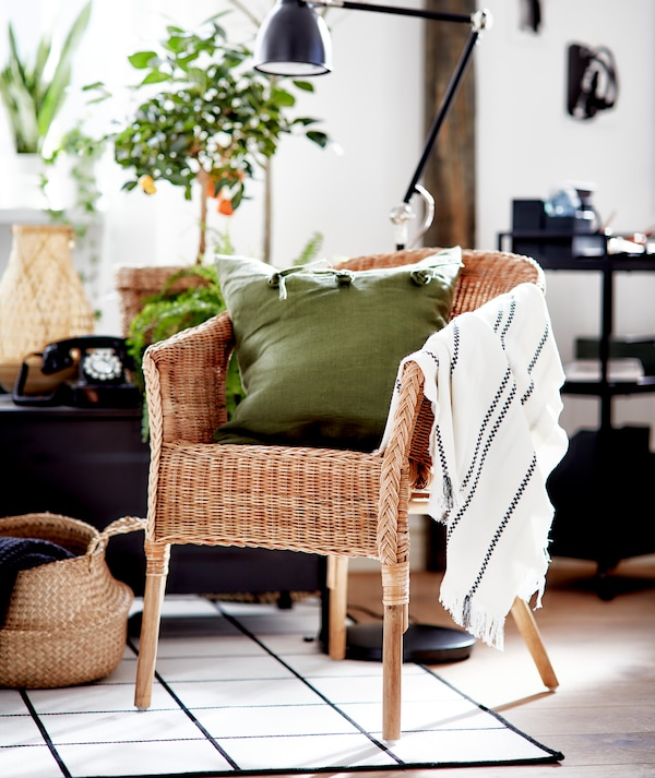 A living room in graphic black and white with accents in natural materials and an AGEN rattan chair with a green cushion.