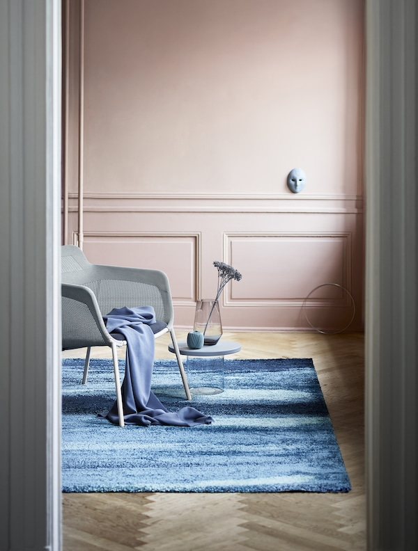 A living room with a blue high pile rug with a pattern that is inspired by waterfalls. Shown together with an armchair and a small table decorated with a vase and dried flowers.