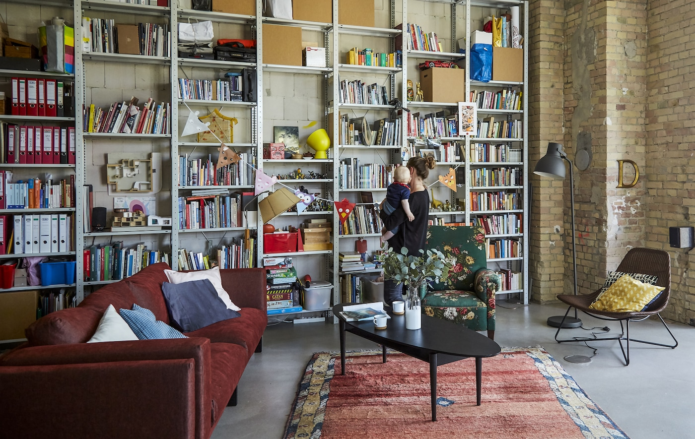 A living room with a red sofa and wall of shelves.
