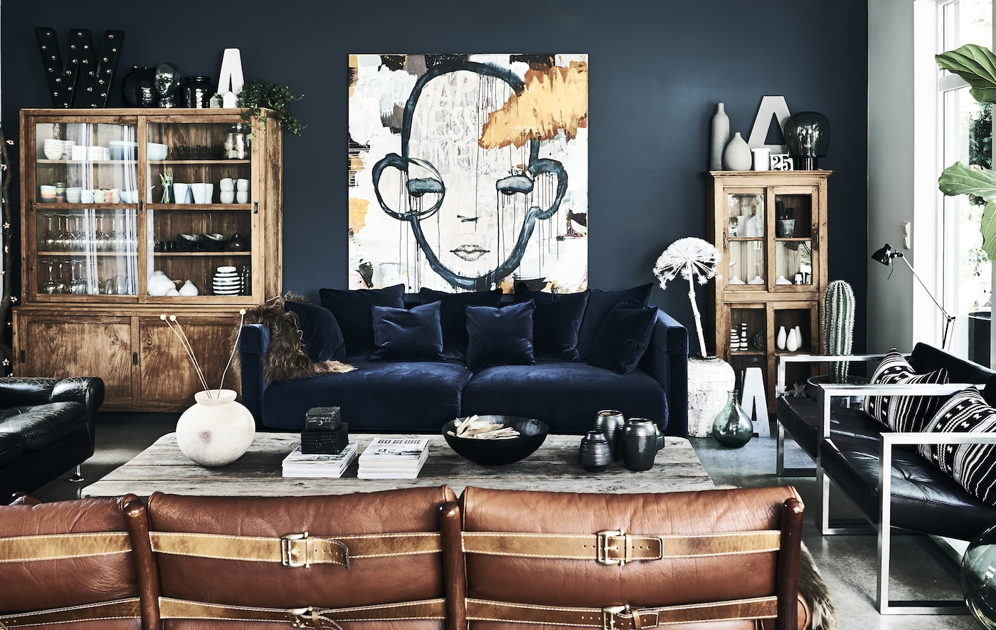 A living room with blue velvet sofa and dark walls.