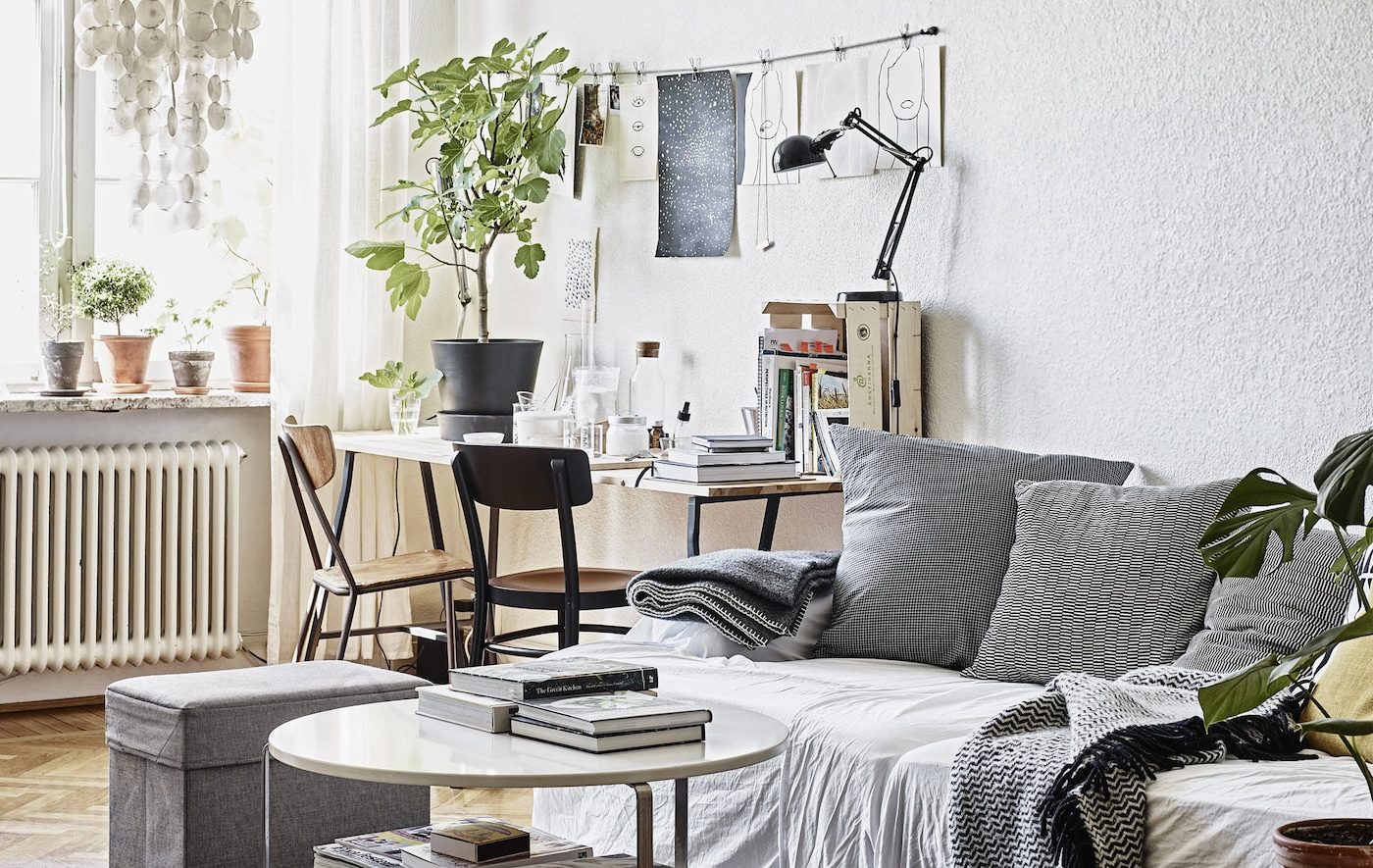 A living room with sofa and desk in neutral colours.