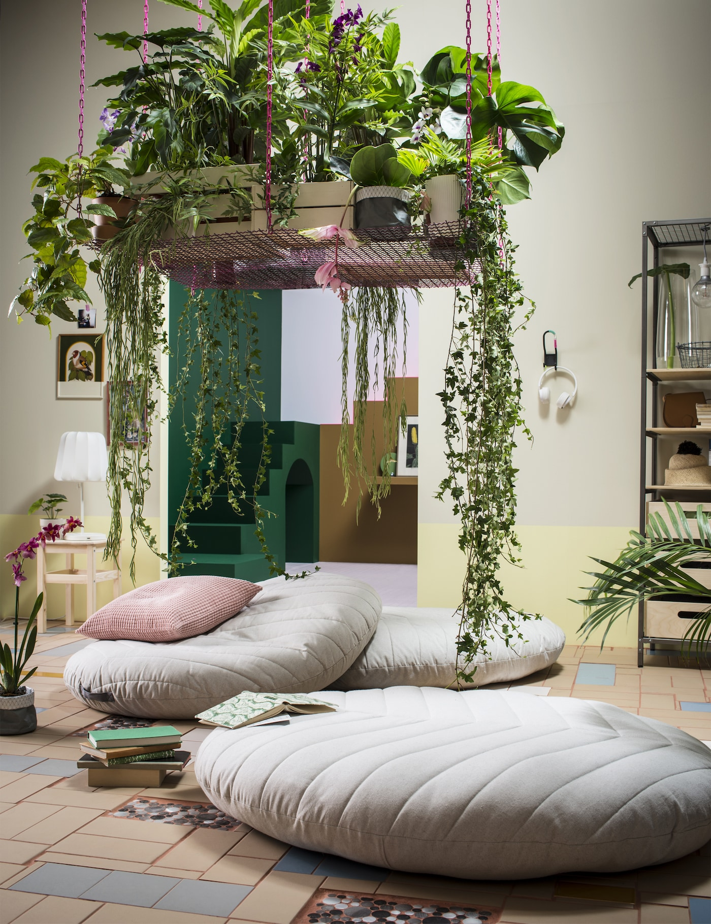 A living room with three large floor cushions in beige cover, above the cushions a hanging shelf with various green plants.