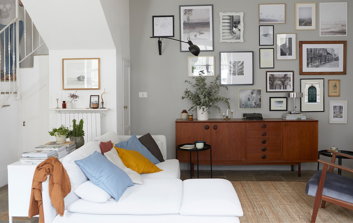 A living room with white corner sofa, dark wooden sideboard and gallery of pictures on the wall.