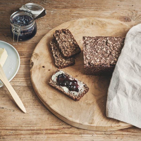 A loaf of KNÅDA multigrain bread with cut slices on a wooden plate placed on a wooden table with butter and jam.