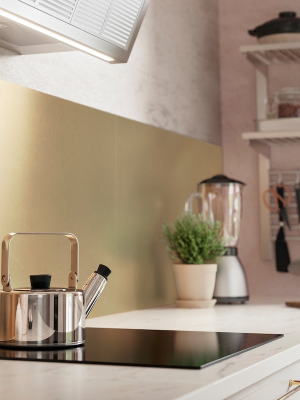 A LYSEKIL brass coloured wall panel behind a kitchen worktop with marble effect and a stainless-steel tea pot on a hob.