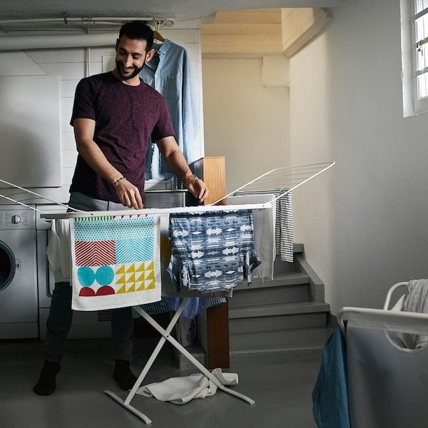 A man hanging laundry in the basement using the drying rack MULIG.