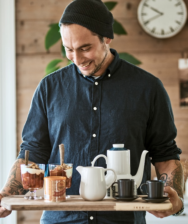 A man in a wool hat uses a chopping board as a tray to carry in a breakfast coffee pot, espresso cups and granola in a glass.