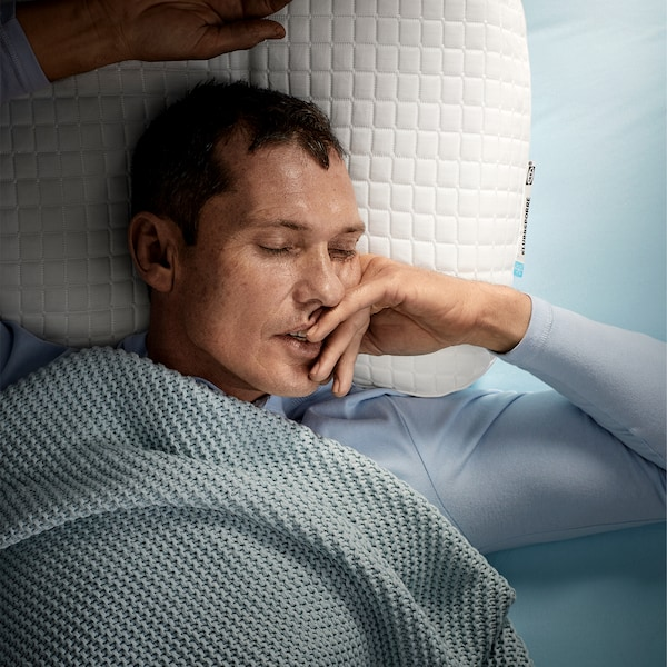 A man, laying on his back, is sleeping deeply on IKEA KLUBBSPORRE ergonomic pillow.