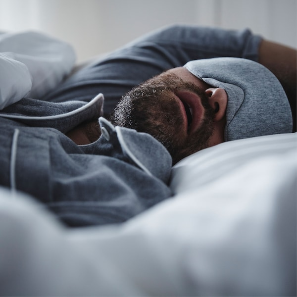 A man wearing blue pyjamas and matching eye-mask lies asleep in bed with his mouth open.