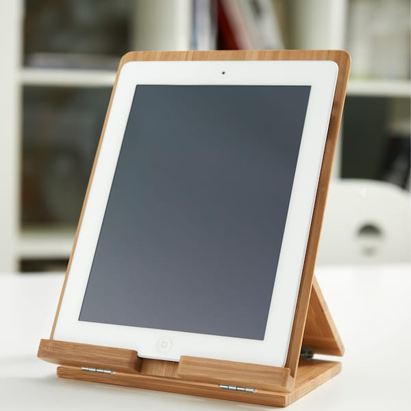 A mobile device screen on a wooden holder, placed on a desk or similar work-top.