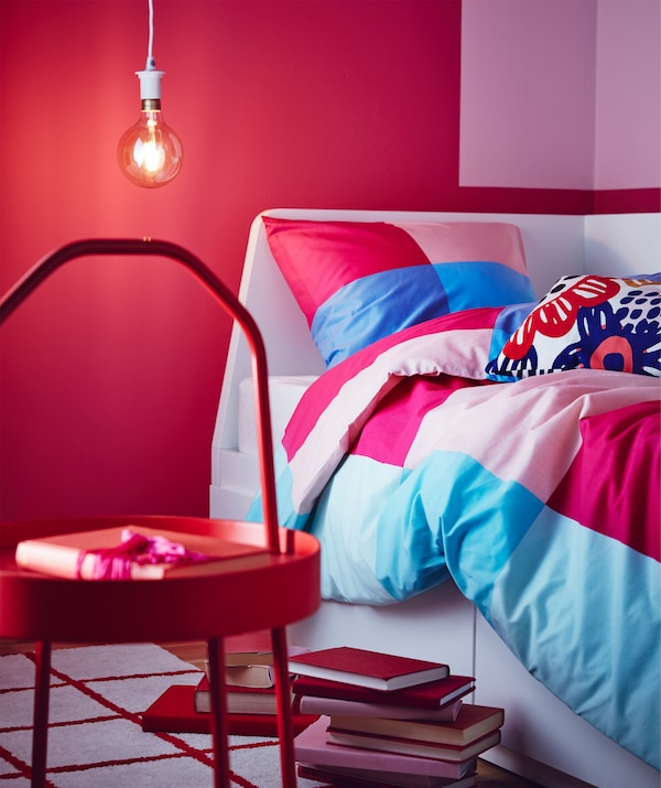 A multicolour IKEA BRUNKRISSLA quilt cover and pillowcase with a pattern of big squares in different pink and blue hues.