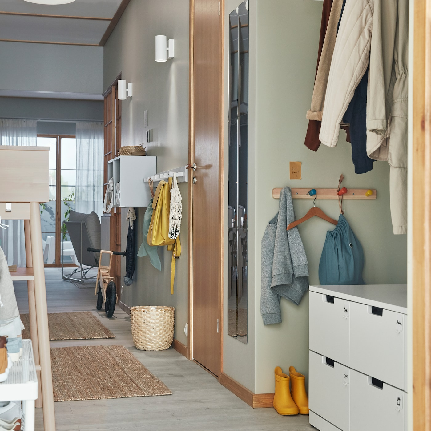 A narrow hallway with smart storage, like racks with hooks and chest of drawers, for both grown-ups and children.