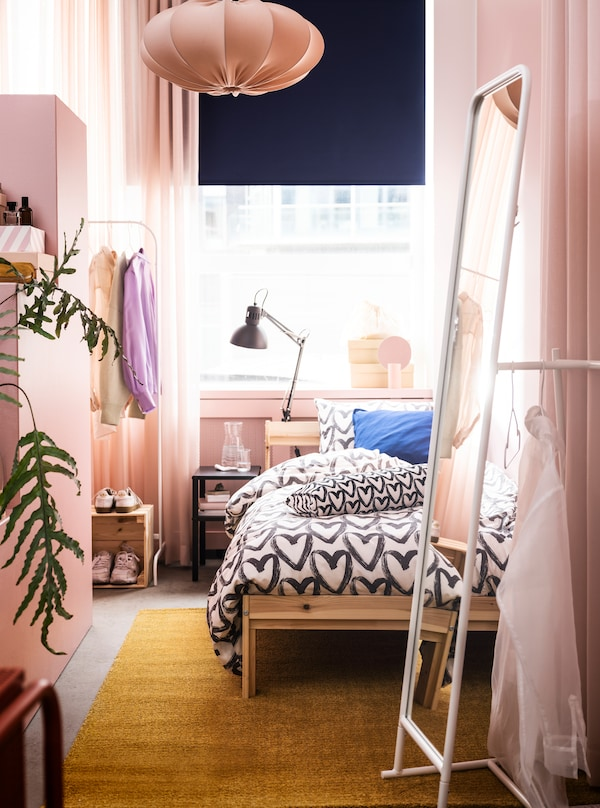 A narrow room in a rosy colour scheme with a GRIMSBU bed, a tall KNAPPER mirror and ample room to store and display clothes.