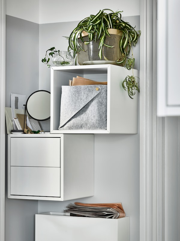 A narrow wall beside a door with white, wall hung EKET cabinets, one open and the other with drawers and with plants on top.