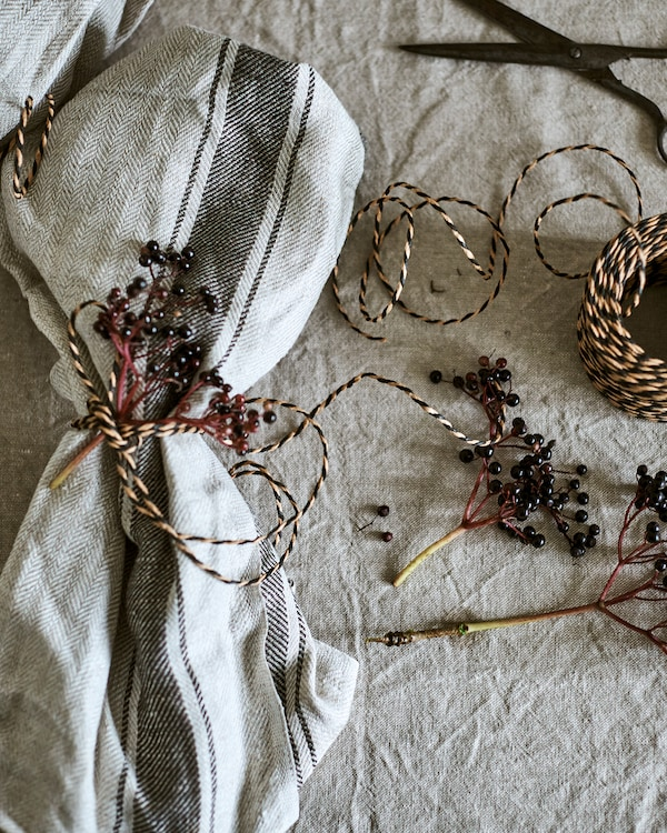 A natural coloured tea towel used as a napkin and decorated with twine and wild berries. A ball of twine is at the side.