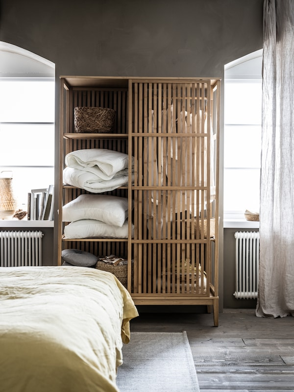 A NORDKISA open wardrobe filled with duvets, pillows, decorations and clothes stands in-between two bedroom windows.