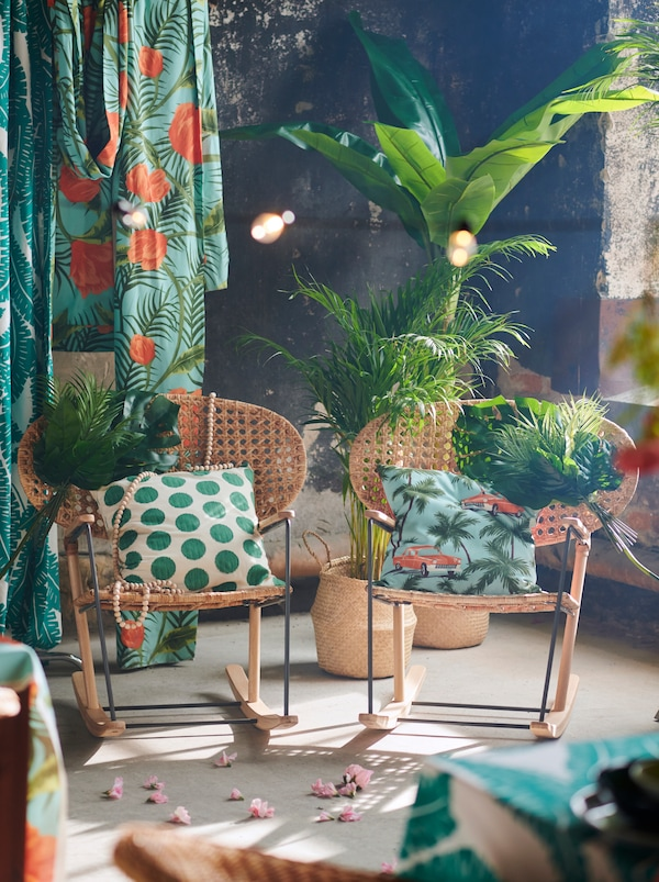 A pair of decorated GRÖNADAL rocking chairs side by side, surrounded by colourful textiles, tropical plants and flowers.