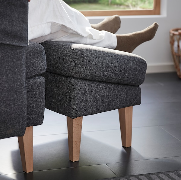 A pair of legs and feet resting on the OMTÄNKSAM footstool. Thanks to its angle it doesn't disrupt blood circulation.