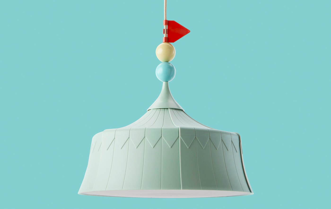A pale green pendant light with circus tent design on a turquoise backdrop.