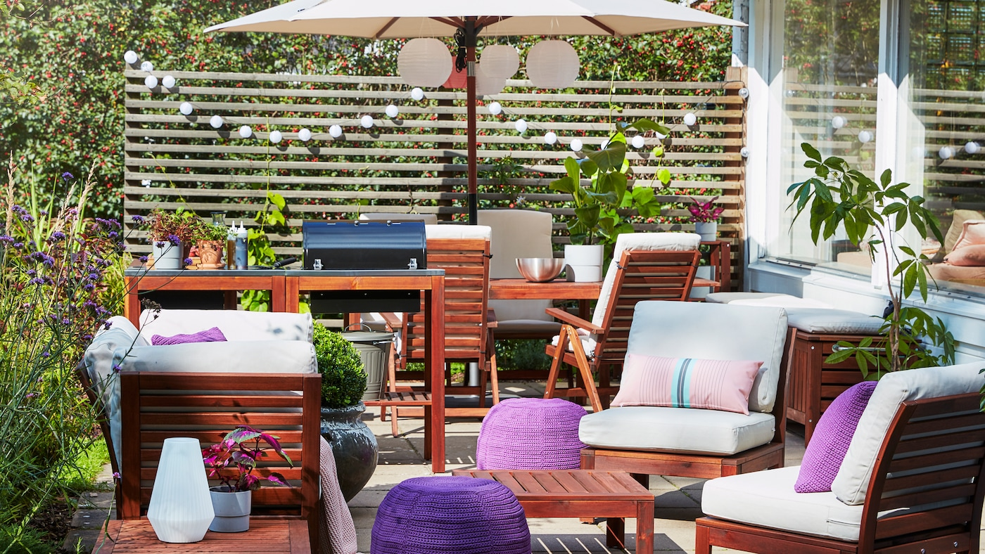 A patio with a barbecue, a 4-seat conversation set, a beige parasol, purple pouffes and beige outdoor cushions.