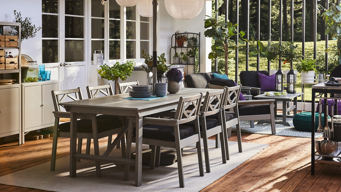A patio with a table and chairs with armrests in grey, storage, round pendant lamps and a wooden floor.