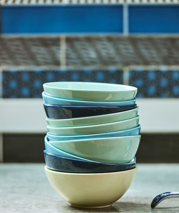 A pile of bowls in shades of turquoise and dark and light blue on a concrete worktop with patterned blue wall tiles.