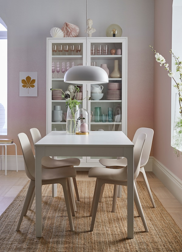 A pink and white dining area with EKEDALEN white table surrounded by ODGER white/beige chairs.