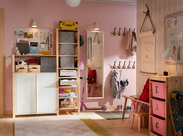 A pink and white hallway with the practical 3-section IVAR with cabinet and shelves in solid wood used as storage, paired up with a white SKDIS pegboard.