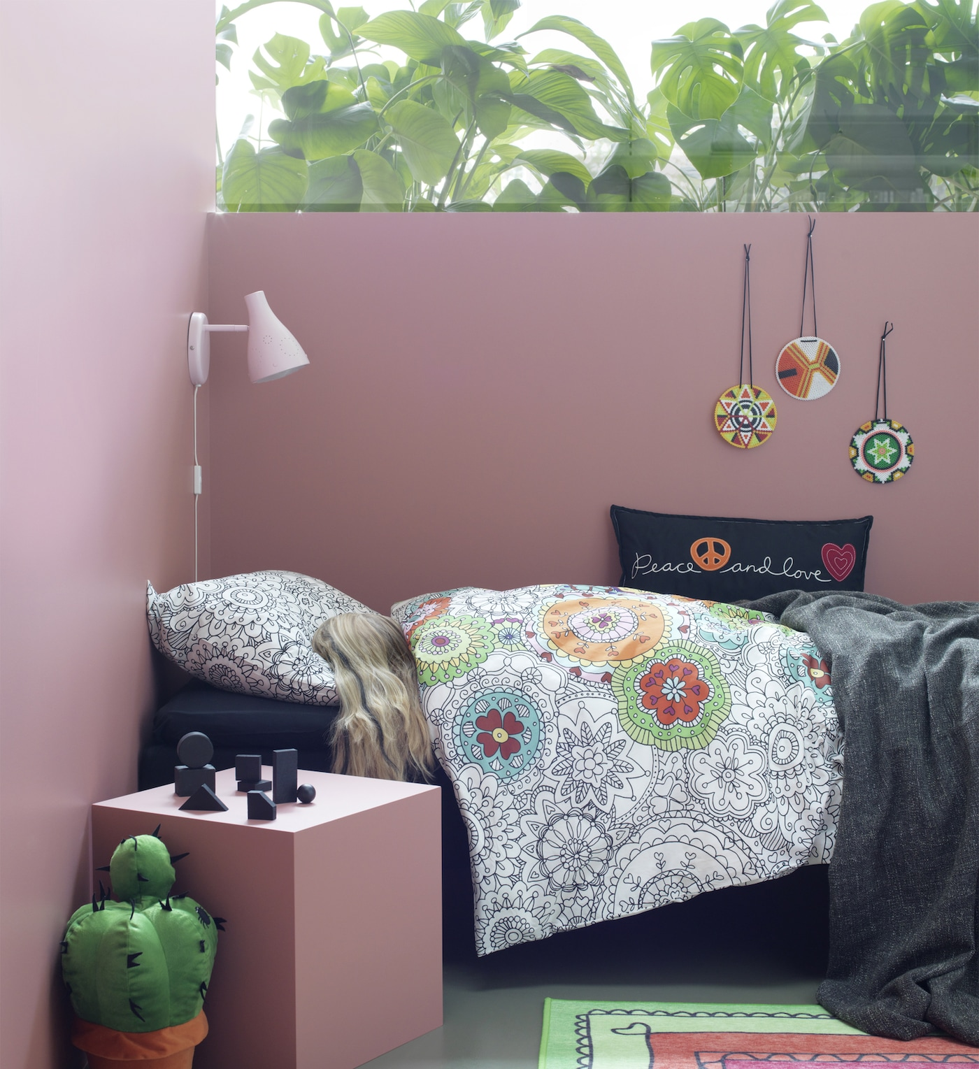 A pink room with a girl sleeping under a quilt cover with mandala-pattern. In the bed there is also a black throw cushion with peace and love text and symbols.