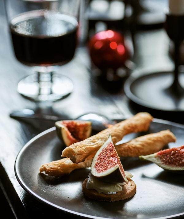 A plate of party food with fig, cheese, biscuits and breadsticks, on a table with a glass of wine and red Christmas bauble.