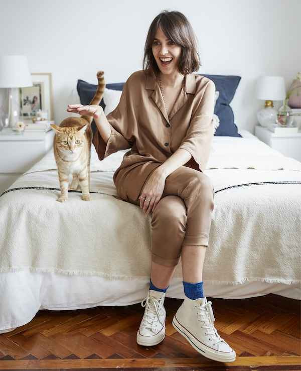 A portrait of Carolina sitting on her bed with her cat.