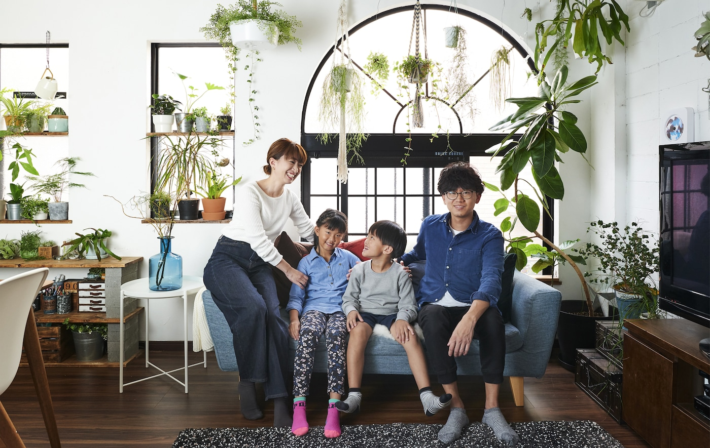 A portrait of Hiromi and Shunsuke and their children sitting on the sofa and plants displayed in the windows behind.