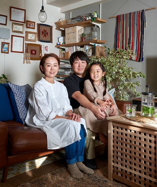 A portrait of Mieko, Kenta and their daughter sitting on the sofa.