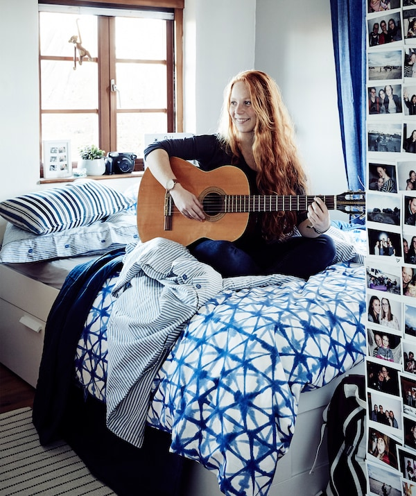 A portrait of Stine playing the guitar on her bed.