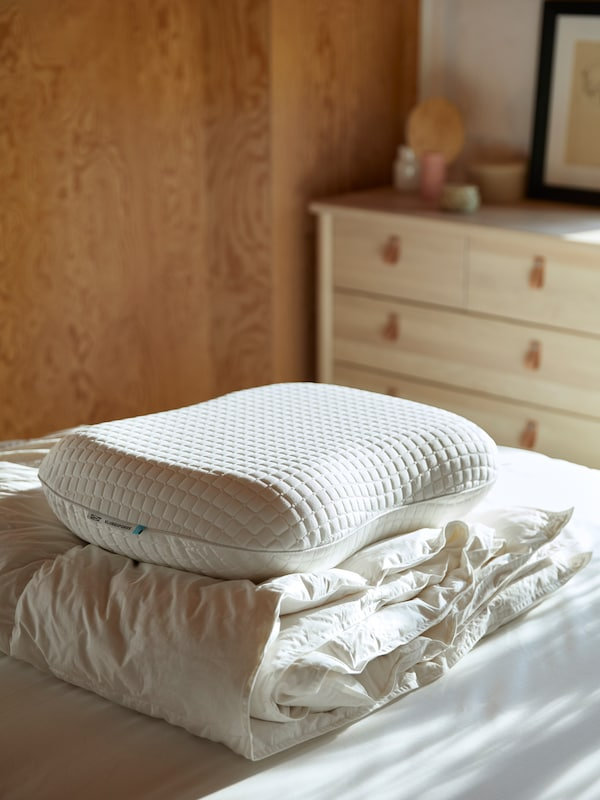 A quilt and KLUBBSPORE pillow are piled-up together on a clean white duvet within a sun-filled room.