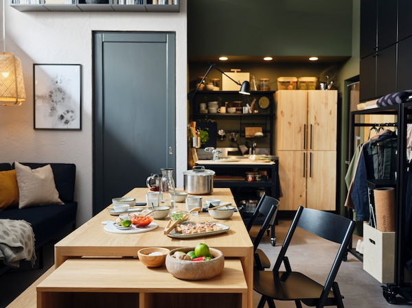A RÅVAROR table, storage unit, and folding chairs are situated in the middle of an apartment. There is crockery on the table.