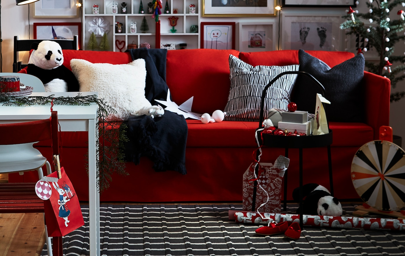A red, black and white living room with plenty of personal details and flexible furniture creates a warm and cosy atmosphere.