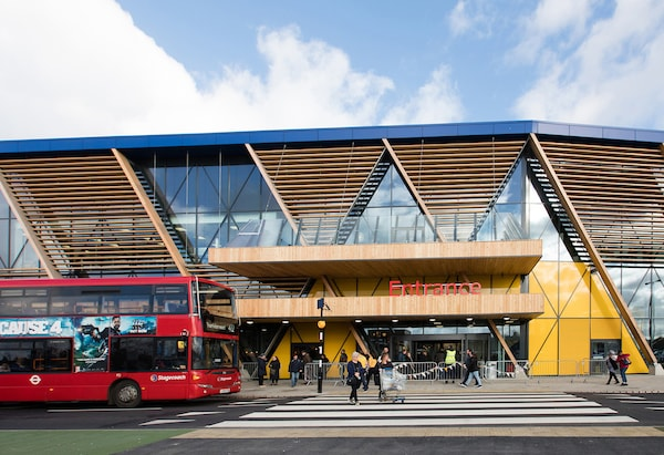 A red bus drives past the new IKEA Greenwich store in London with wooden and glass frontage.