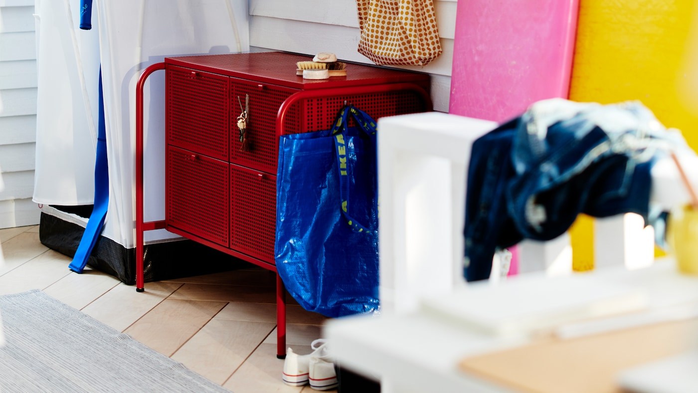 A red NIKKEBY chest of drawers surrounded by various hallway accessories in a clapboarded, white room.