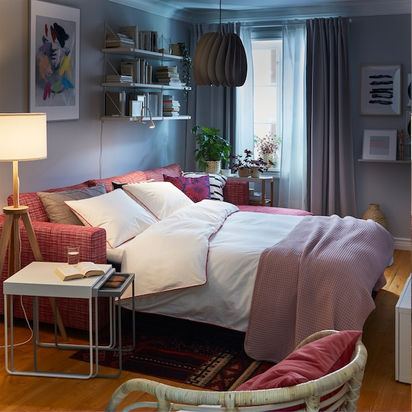 A red sofa-bed made as a bed with white bed textiles, a white nest of tables and a wooden and white floor lamp.