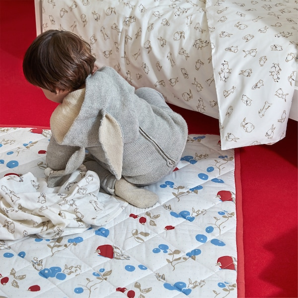 A RÖDHAKE quilted blanket with a rabbit and blueberry pattern on a light-coloured background.