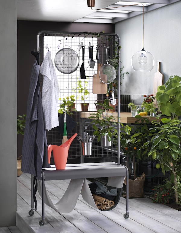A room divider in grey steel on castors. Mesh with hooks at the top, propped with kitchen utensils, and a shelf with two hanging organisers in a cotton/linen blend at the bottom, propped with place mats.